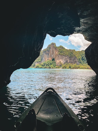 boat emerging from cave in thailand