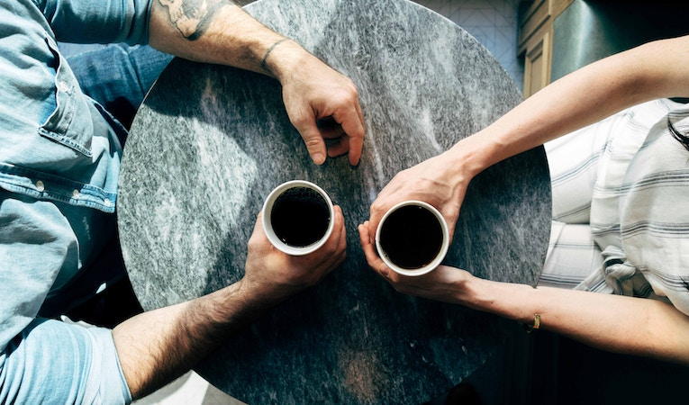 two people drinking black coffee