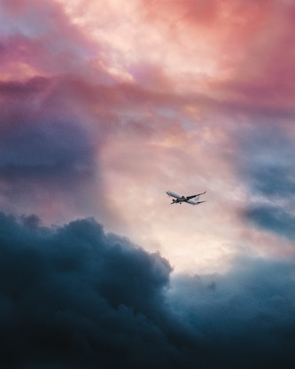 airplane silhouetted by clouds