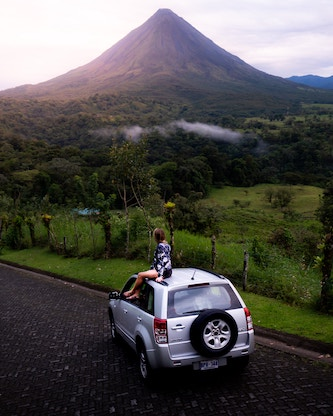 person sitting on car looking at arenal volcano in costa rica