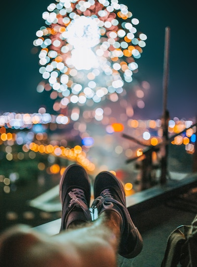 person's feet silhouetted by fireworks