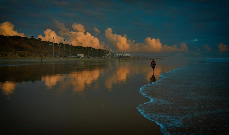 person walking along beach in spain