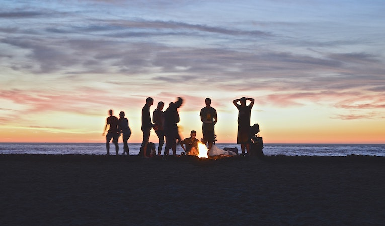 people at a bonfire on the beach